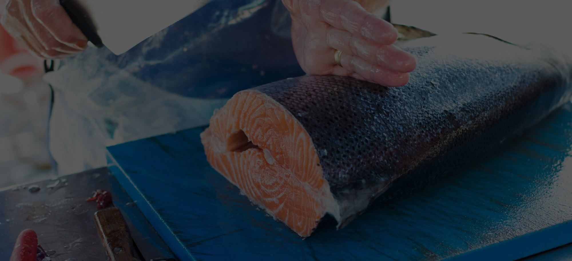 Man cutting salmon in half